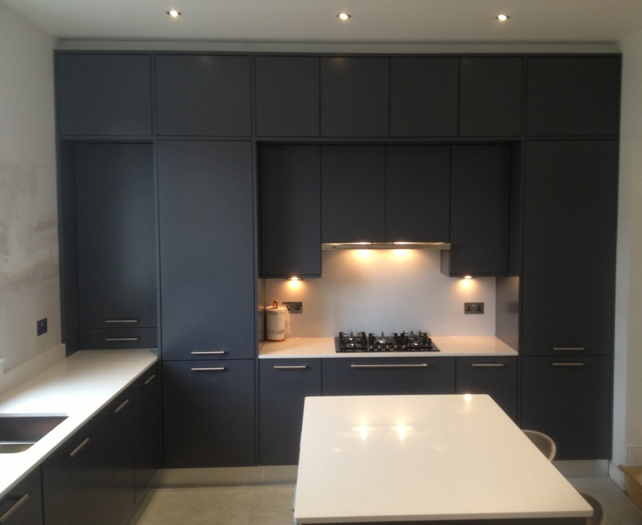 Grey spray painted kitchen with stainless steel plinth